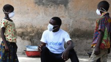 In Côte d'Ivoire and UNICEF staff member talks to kids about wearing a mask to protect against COVID-19.