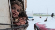 Children peer out from a tent at a settlement for displaced families who have fled violence in souther Idlib and rural Aleppo in northwest Syria in January 2020.