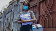 Health worker Arlette Nyange carries vaccines in a cold box during a UNICEF-supported immunization campaign in Kinshasa, DR Congo.