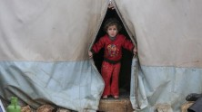 On January 19, 2021, a child peers out of a tent in Kafr Losin Camp in northwestern Syrian Arab Republic