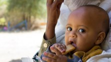 Natan, the youngest member of a family displaced by the violence in Ethiopia's Tigray region, eats a nutritional biscuit supplied by UNICEF.