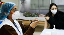 A vaccinator administers a COVID-19 vaccine to a health worker at Lok Nayak Hospital in New Delhi, India.