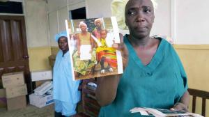 n July 2014 in Sierra Leone, Sister Nancy Yoko holds a photograph of survivors of Ebola virus disease (EVD) who left a treatment centre the previous week.