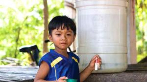 A boy stands with a ceramic filter by a water pump in Cambodia.
