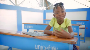 Gloria is smiling at a UNICEF desk
