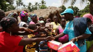 To raise awareness of the Ebola virus in Liberia, UNICEF communicators distribute educational materials.