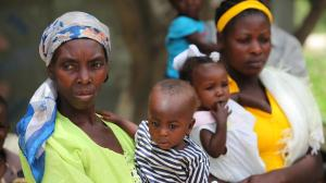 A mother holds her child at the mobile vaccination station set up outside a church by the side of a road in Haiti