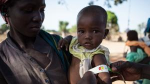 A doctor from the Alliance Médicale Contre le Paludisme (AMCP, the Medical Alliance against Malaria) uses an armband to measure the mid-upper arm circumference of a small child while a woman holds her.
