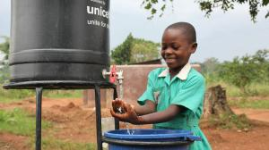 A young girl washes her hands with soap after using the latrine in Uganda.