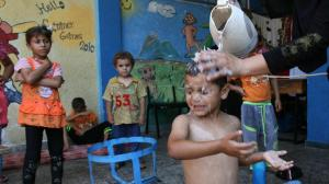 A woman uses water from a pitcher to bathe her son in Gaza. © UNICEF/NYHQ2014-1049/El Baba