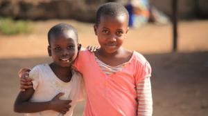 2 young girls stand at the Treasure Life Centre in Uganda.