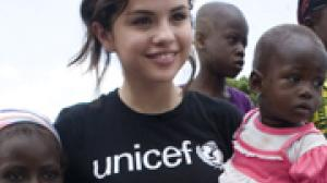 Selena Gomez holds a young child in her arms in Ghana