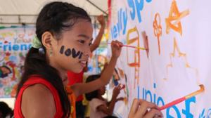 A girl paints a sign with the UNICEF logo in the Philipines. She has love written on her face.