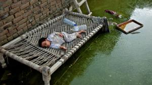 On 4 August, a child sleeps on a charpai, a traditional woven bed, surrounded by floodwater in his home in Khwas Koorona Village, Khyber-Pakhtunkhwa Province. An estimated 2.5 million of the province's 3.5 million residents have been affected by the flood