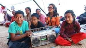 "Nepal Earthquakes 2015: Children listen to a segment of the UNICEF-supported ""Bhandai-Sundai"" radio program at an informal camp for people displaced by the April 25 earthquake."