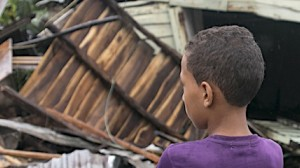 A boy, 7, looks at a damaged home in the Dominican Republic after Hurricane Irma