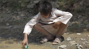 A child plays with a container cap in untreated water coming from a sewer pipe in Amran Governate, Yemen, October 2017.