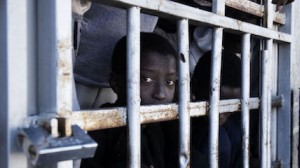 Child migrant looking through the bars of a detention cell in Libya.