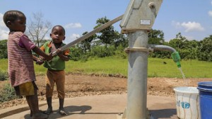 Three-year-old Innocent (right) and a friend use a new hand pump to fill a container with safe, clean water in Rutana Province, Burundi in January 2018.