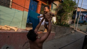 A father holds his infant son, Santiago, in San Salvador, El Salvador.