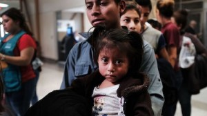 A Guatemalan father and his daughter arrive with dozens of other women, men and children at a bus station following release from Customs and Border Protection in McAllen, Texas.