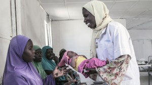 A health worker returns baby Aishat to her mother Hausa at a UNICEF-supported health clinic in the Muna Garage displacement camp, Maiduguri, Borno State, northeast Nigeria.