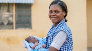 Community health worker Amilia Mathew holds a baby she delivered at a UNICEF-supported clinic in Yola, Nigeria in 2018.