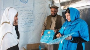 A grateful student smiles as UNICEF Education Specialist Anita Haidary, far right, and colleague distribute new school bags and notebooks during a visit to the Zanogra Community-Based Education (CBE) cluster in Surkhrod district, Nangarhar province, Afgha