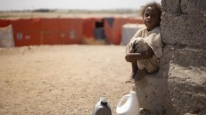 A child from Yemen's Al-Meshqafah camp takes a break while carrying heavy jugs of drinking water from supply tanks to the camp.