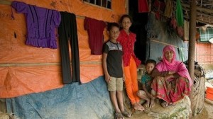 On July 11, 2019, 11-year-old Jannatul Noor (in orange pants) stands with her family outside their shelter in Jamtoli camp, Cox's Bazar, Bangladesh. Their home was partially damaged during recent monsoon rains.