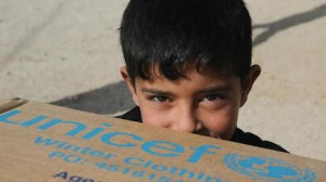 A young Syrian refugee receives warm winter clothing from UNICEF.