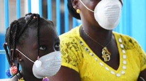 A mother and daughter, photographed at a health center in Port Bouet, a suburb of Abidjan in the south of Côte d'Ivoire, wear masks to protect against COVID-19.