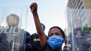 In Atlanta, a young boy raises his fist for a photo by a family friend during a May 31, 2020 demonstration following the death of George Floyd while in police custody.