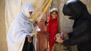 A UNICEF-trained health worker vaccinates a child against polio outside the family's home in Quetta, Balochistan Province, Pakistan.