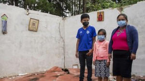 Thirteen-year-old Hernan and Dafne, 7, stand with their mother, Sonia, amid the wreckage of their home in Guatemala, destroyed by Hurricanes Eta and Iota.