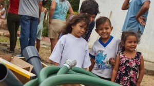 Children watch as UNICEF staff and partners install a water tank which will provide access to safe water to an estimated 24,000 people a month in San Antonio, Tachira state, Venezuela.