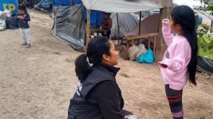 UNICEF Mexico Deputy Representative Pressia Arifin-Cabo kneels down to speak with a child at an encampment in Matamoros in the northeastern state of Tamaulipas.