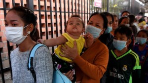 People wearing face masks line up to enter a children's hospital in Phnom Penh, Cambodia on January 30, 2020 after the nation's first case of novel coronavirus was reported.