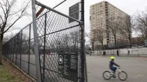 On March 17, 2020, a child rides a bike through an empty playground outside Public School 24 in the Riverdale neighborhood of the Bronx, New York City, during the coronavirus pandemic.