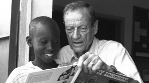 """Former UNICEF USA Executive Director James P. """"Jim"""" Grant shares a book with a boy at a community center near Abidjan, Côte d'Ivoire."""
