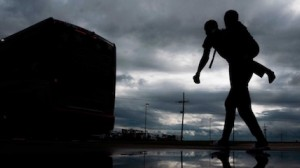 A man carries a child on his back as he walks to board a bus for evacuation before the arrival of Hurricane Laura in Lake Charles, Louisiana on August 25, 2020.