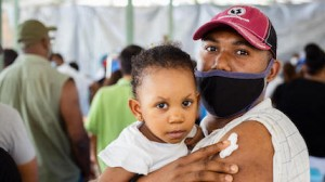 Hervé Ternier, holding his 19-month-old daughter, Rosaika, received his COVID-19 vaccine at a UNICEF-supported vaccination site in Port-au-Prince, Haiti on July 24, 2021.
