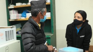 Mitthi Jirel (left), staff at the district hospital in Jiri in Dolakha District in northeastern Nepal, shows UNICEF staff Preena Shrestha a vaccine carrier in the hospital's vaccine storage room on February 26, 2021.