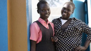 On February 3, 2021, Keziah, 14, (left) and Elizah, 16, stand in front of a newly rehabilitated latrine at AIC Nursery and Primary School in Torit, South Sudan.