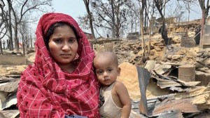 On March 23, 2021, Sharifa holds her infant nephew in her arms as they stand in front of shelters destroyed by a massive fire in the Balukhali area of the Rohingya refugee camps in Cox's Bazar, Bangladesh.