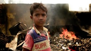 On March 23, 2021,10-year-old Rezwan stands in the fire-damaged wreckage of the Balukhali area of the Rohingya refugee camps in Cox's Bazar, Bangladesh.