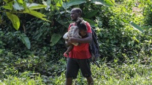 A father and child arrive exhausted after crossing the Darien Gap to Bajo Chiquito, Province of Darien, Panama.