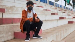 Andre, 14, stands in a repurposed sports stadium in Lima, Peru, waiting for his appointment at the nearby  UNICEF-supported Carabayllo Community Mental Health Center.