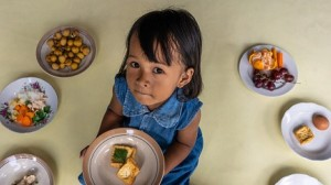 Gelsi, 3, holds a plate of tofu at her home in Paseban Village, Klaten, Central Java Province, Indonesia, on September 8, 2021