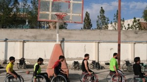 On 22 November 2019, adolescent boys use wheelchairs in an outdoor basketball court at Abdul Ahad Karzai Orphanage in Kandahar, Afghanistan. Many of them have been injured in conflict and have lost limbs in landmine accidents.